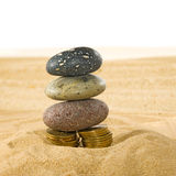 Image of coins and stones on the sand close up Royalty Free Stock Photos