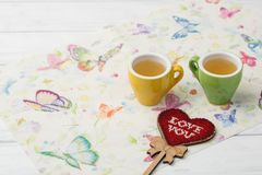 Image of colorful heart shape and couple mugs of tea on a napkin with butterflies. valentine`s day celebration concept. royalty free stock photography