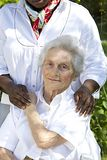Image of comfort and support from a care giver to the Senior. Image of comfort and support from care giver to smiling elderly women outdoor Stock Photos