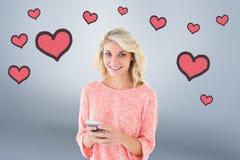 Image composée assez de blond utilisant son smartphone Image libre de droits