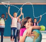 Image composée d'élève mignon souriant tenant le globe Photo stock