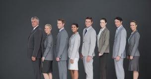 Image composée d'équipe d'affaires se tenant dans la rangée et souriant à l'appareil-photo Image libre de droits