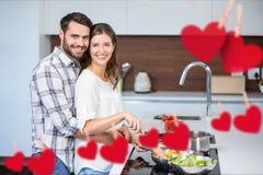 Image composée d'accrocher le coeur rouge et les couples faisant cuire la nourriture Images stock