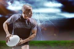 Image composée d'athlète fonctionnant avec la boule de rugby Photographie stock libre de droits