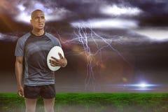 Image composée d'athlète réfléchi tenant la boule de rugby Photos stock