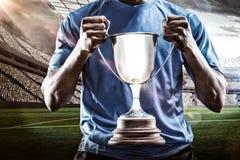 Image composée 3D de la mi section du sportif tenant le trophée Photos stock