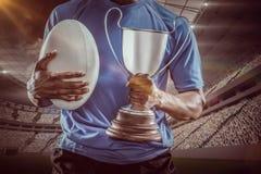 Image composée 3D de la mi section du sportif tenant le trophée et la boule de rugby Photographie stock libre de droits
