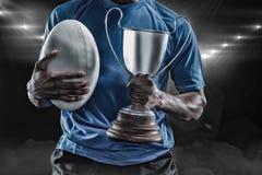 Image composée 3D de la mi section du sportif tenant le trophée et la boule de rugby Image stock