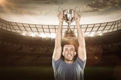 Image composée 3D de portrait du joueur de sourire de rugby tenant le trophée Image stock