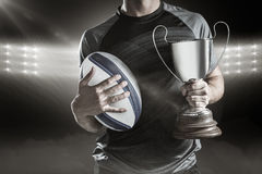 Image composée 3D de section médiane du joueur réussi de rugby tenant le trophée et la boule Image libre de droits