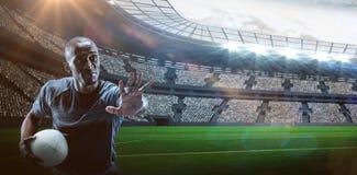 Image composée 3D de sportif sérieux faisant des gestes tout en tenant la boule de rugby photos libres de droits