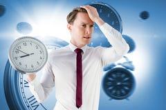 Image composée d'homme d'affaires soucieux tenant une horloge photographie stock libre de droits
