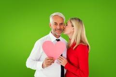 Image composée d'homme bel tenant le coeur de papier obtenant un baiser de l'épouse Image libre de droits