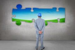 Image composée d'homme d'affaires avec le casque tournant le sien de nouveau à l'appareil-photo Images stock