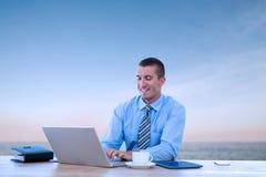 Image composée d'homme d'affaires de sourire travaillant avec son ordinateur portable image stock