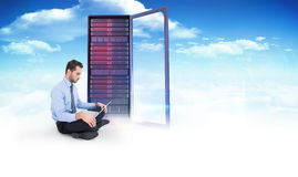 Image composée d'homme d'affaires gai se reposant sur le plancher utilisant l'ordinateur portable Image libre de droits