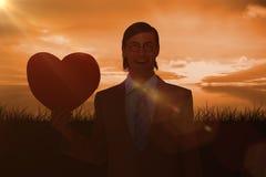 Image composée d'homme d'affaires geeky souriant et tenant la carte de coeur Image stock