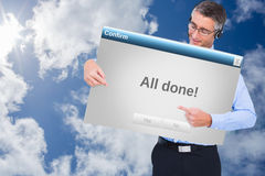 Image composée d'homme d'affaires heureux avec l'écouteur présentant un panneau Photographie stock libre de droits