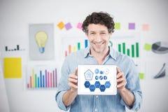 Image composée d'homme d'affaires montrant le comprimé numérique avec l'écran vide dans le bureau créatif photographie stock libre de droits