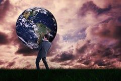 Image composée d'homme d'affaires portant le monde photographie stock libre de droits