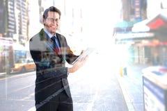 Image composée d'homme d'affaires regardant l'appareil-photo tout en à l'aide de son comprimé Image libre de droits