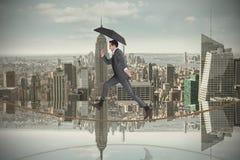 Image composée d'homme d'affaires sautant sur la corde raide tenant un parapluie Photo libre de droits