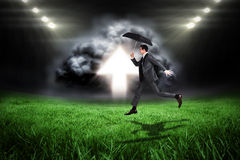 Image composée d'homme d'affaires sautant tenant un parapluie Image stock