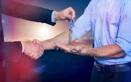 Image composée d'homme d'affaires se serrant la main et donnant des clés Image stock