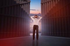 Image composée d'homme d'affaires se tenant de nouveau à l'appareil-photo avec des mains sur la tête 3d Image stock