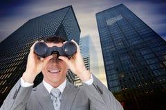 Image composée d'homme d'affaires tenant des jumelles photographie stock libre de droits
