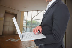 Image composée d'homme d'affaires tenant l'ordinateur portable Photo libre de droits