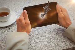 Image composée d'homme d'affaires tenant le petit comprimé à la table 3d Images libres de droits