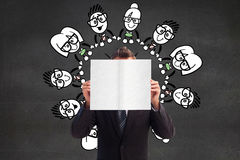 Image composée d'homme d'affaires tenant une carte blanche devant son visage Image stock