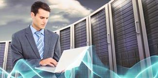Image composée d'homme d'affaires utilisant l'ordinateur portable avec des collègues derrière Photographie stock libre de droits