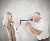 Image composée d'homme fâché criant à l'amie par le mégaphone Image stock