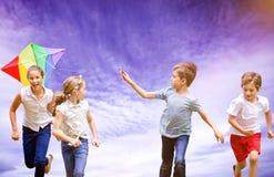 Image composée d'intégral du garçon tenant le cerf-volant fonctionnant avec des amis Image stock