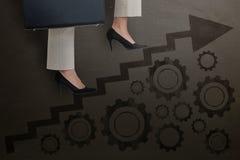 Image composée de basse section des étapes s'élevantes de femme d'affaires avec la serviette Photos stock