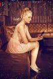 Image composée de belle femme se reposant sur le sofa et à l'aide du téléphone portable image stock