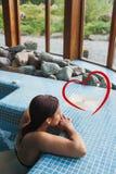 Image composée de brune détendant dans un jacuzzi Images stock