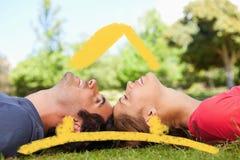 Image composée de deux amis de sourire avec leurs yeux fermés tout en se trouvant tête à tête Photographie stock libre de droits