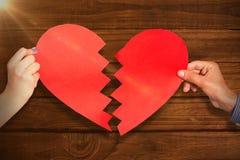Image composée de deux mains tenant le coeur brisé Photos libres de droits