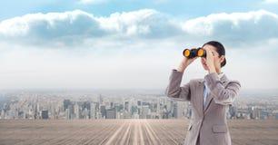 Image composée de Digital de femme d'affaires regardant par des jumelles photographie stock