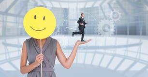 Image composée de Digital de femme d'affaires tenant le smiley tandis qu'homme d'affaires courant sur sa main Photographie stock