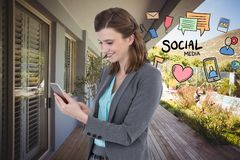 Image composée de Digital de la femme d'affaires à l'aide du téléphone intelligent par de diverses icônes tout en se tenant contr Photos stock