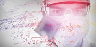 Image composée de docteur dans les verres protecteurs et le masque chirurgical tenant la puce électronique photographie stock libre de droits