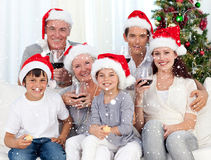 Image composée de famille célébrant Noël avec du vin et des bonbons Image stock