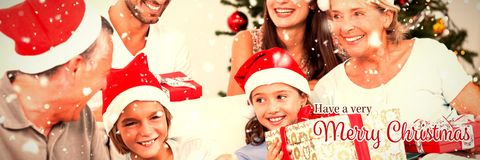 Image composée de famille heureuse à Noël permutant des cadeaux image stock