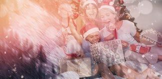 Image composée de famille heureuse aux cadeaux d'ouverture de Noël ensemble Photo stock