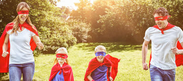 Image composée de famille heureuse feignant pour être fonctionnement de super héros illustration libre de droits