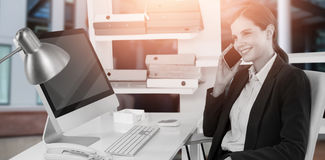 Image composée de femme d'affaires de sourire parlant au téléphone portable au bureau avec l'ordinateur images stock